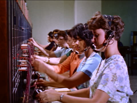 1960s row of female telephone operators in headsets working at switchboard / educational - telephone switchboard stock videos and b-roll footage