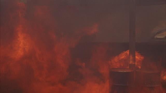 1960s ws rural gas station on fire - stahlfass stock-videos und b-roll-filmmaterial