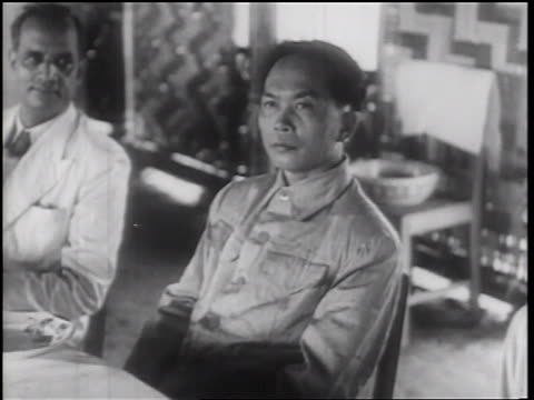 1960s serious vietnamese man sitting at table / north vietnam - 30代の男性だけ点の映像素材/bロール