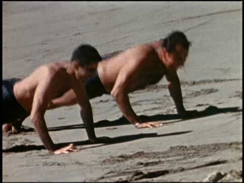 1960s shaky medium shot 2 men doing pushups on beach / california - home movie stock videos & royalty-free footage