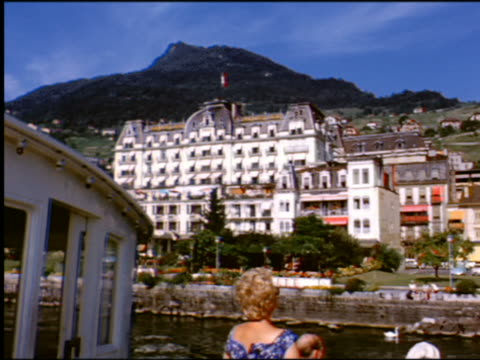 1960s side boat point of view past grand hotel + surrounding buildings / lake geneva / montreux, switzerland - montreux stock videos and b-roll footage