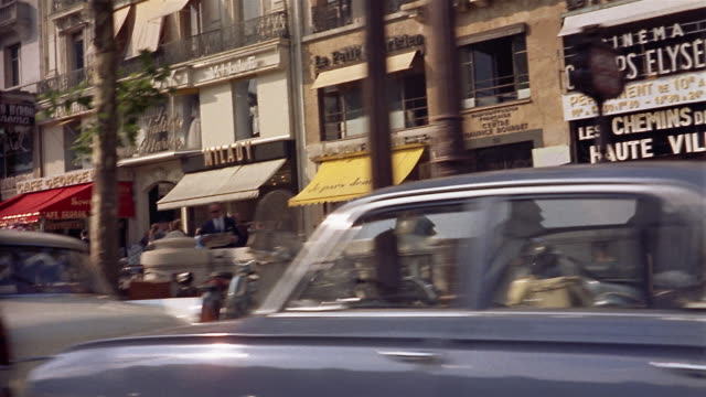 1960s side car point of view stores, pedestrians and cars on Parisian street / Paris, France