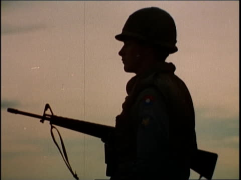 1960s silhouette of first infantry division soldier standing guard at sundown / vietnam - infantry stock videos & royalty-free footage