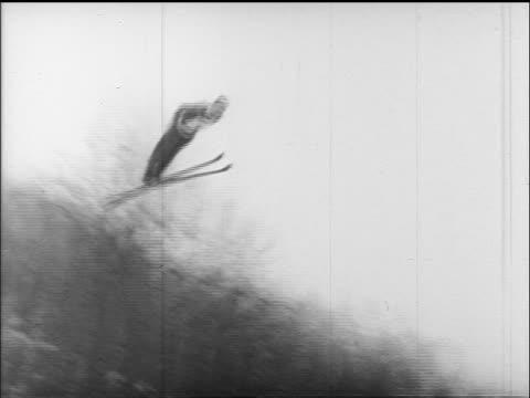 b/w 1960s pan skier doing long ski jump wiping out past bottom / germany / educational - falla av bildbanksvideor och videomaterial från bakom kulisserna