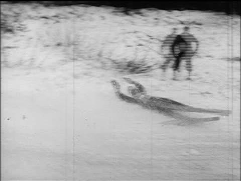 b/w 1960s pan skier sliding down slope on back / germany / educational - falla av bildbanksvideor och videomaterial från bakom kulisserna