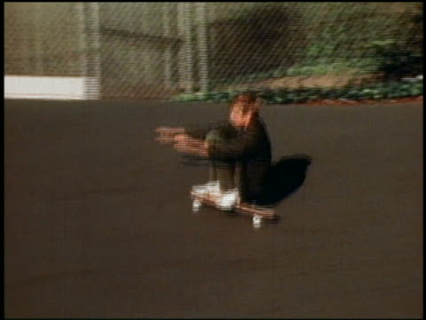 1960s slow motion medium shot tracking shot boy skateboarding / other children watching in background - skateboard stock videos and b-roll footage