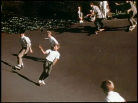 vídeos y material grabado en eventos de stock de 1960s slow motion medium shot tracking shot group of boys skateboarding - de archivo