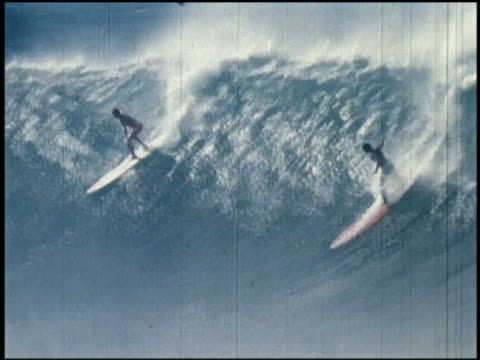 1960s slow motion wide shot tracking shot 2 surfers riding large wave / one surfer falling / california - contestant stock videos & royalty-free footage