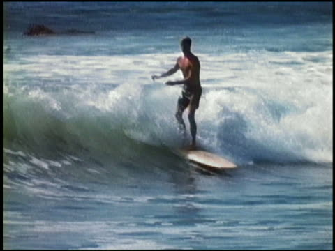 """1960s slow motion wide shot tracking shot surfer riding wave, """"hanging 10"""" / california - surfing stock videos & royalty-free footage"""