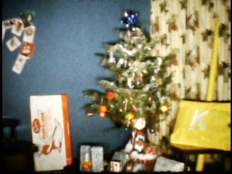 1960s WS Small decorated Christmas tree with train set running around / Lompoc, California, USA