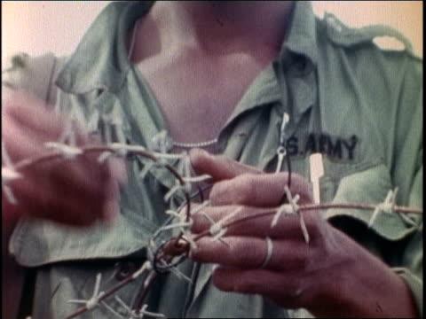 1960s zo soldier working on rolls of barbed wire / vietnam - ブービートラップ点の映像素材/bロール