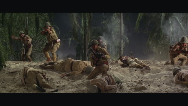 1960s ws soldiers advancing through forest during battle - pericolo video stock e b–roll