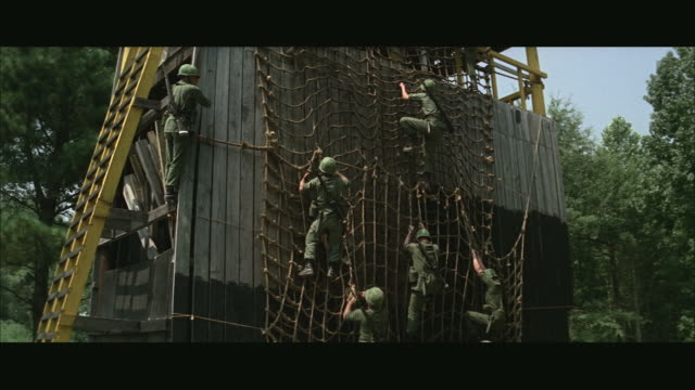 1960s ws la tu soldiers climbing rope ladder during obstacle course at army camp - 障害物コース点の映像素材/bロール