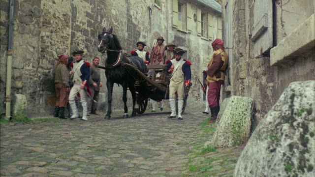 vídeos de stock, filmes e b-roll de 1960s ws soldiers escorting horse cart down alley, punching disrespectful peasant - 1960 1969