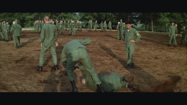 vidéos et rushes de 1960s ms pan soldiers in training at army camp - seulement des jeunes hommes