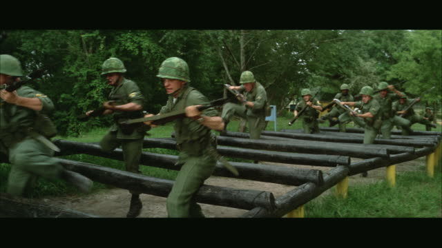 vídeos de stock, filmes e b-roll de 1960s ws soldiers running over hurdles during obstacle course at army camp - campo de treinamento militar
