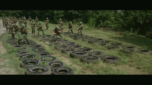 vídeos de stock, filmes e b-roll de 1960s ws soldiers running through tires during obstacle course at army camp - campo de treinamento militar