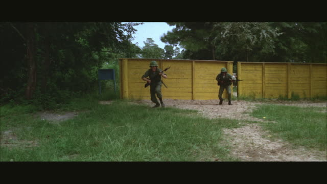 1960s ws soldiers training on obstacle course at army camp - 障害物コース点の映像素材/bロール