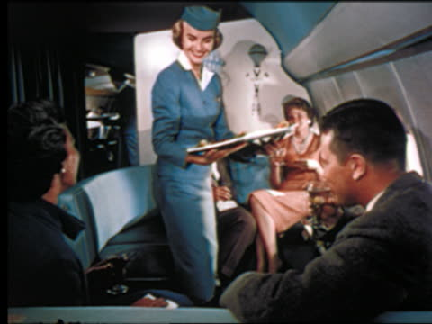 1960s stewardess serving hors d'oeuvres on tray to people with drinks on airliner