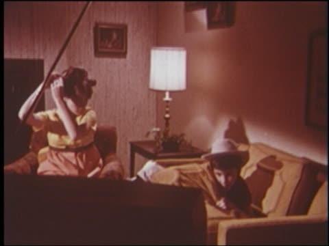1960s teen girl puts curlers in hair, boy in cowboy costume sits on sofa in front of television - cowboy stock-videos und b-roll-filmmaterial