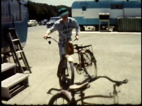 1960s WS Teenage boy exiting trailer with baseball uniform on, getting on bike and riding away / Lompoc, California, USA