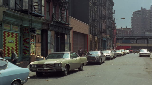 1960s ws tenement street with row of cars / new york city, usa - 1960 1969 stock-videos und b-roll-filmmaterial