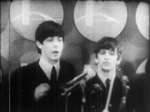 vídeos de stock e filmes b-roll de the beatles brief ms musicians paul mccartney ringo starr standing at microphones talking ms crowds of women females screaming beatlemania fandom... - the beatles