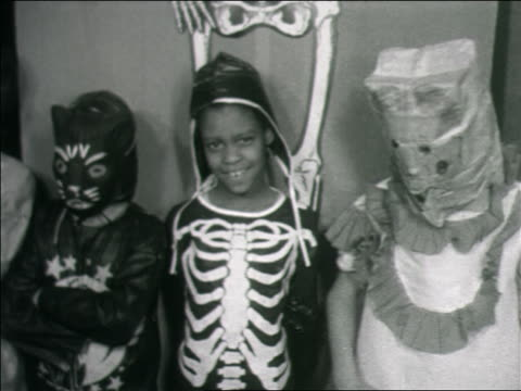 b/w 1960s three children in halloween costumes posing for camera indoors / home movie - halloween stock videos & royalty-free footage