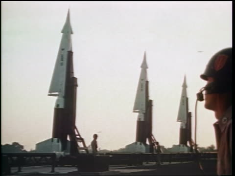 1960s three missiles in line on launch pads / Cold War / documentary