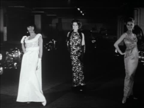 B/W 1960s three women posing in evening dresses as Jaguar pulls up behind them + turns on headlights