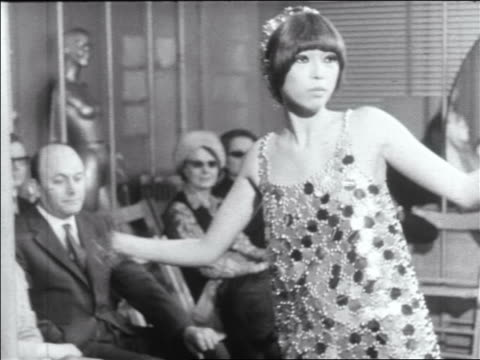 B/W 1960s tilt down Asian woman modeling metal mini-dress dancing in runway show / newsreel