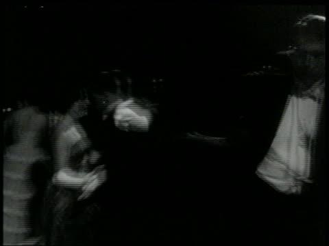 B/W 1960s tilt down couple in formalwear doing the Twist on dance floor