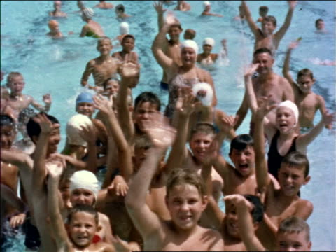1960s tilt down crowd of children in swimsuits in swimming pool waving to camera / los angeles / edu. - freibad stock-videos und b-roll-filmmaterial