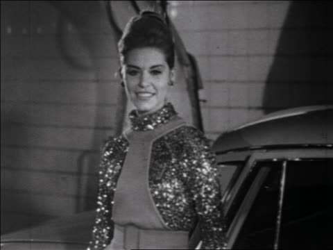 b/w 1960s tilt down from head to feet of woman modeling glittery dress + stockings posing next to car - stockings stock videos & royalty-free footage