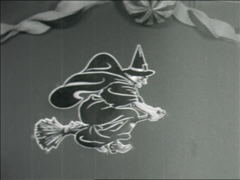 b/w 1960s tilt down from witch decoration to frowning black/hispanic girl in witch hat / home movie - witch stock videos & royalty-free footage