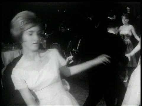 B/W 1960s tilt up PAN couples in formalwear dancing the Twist on dance floor