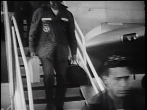 stockvideo's en b-roll-footage met b/w 1960s tilt up soldiers carrying luggage walking down stairs from c135 cargo plane / vietnam war - terugkomdag