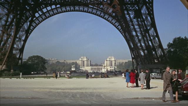 1960s WS Tourists under Eiffel Tower / Paris, France