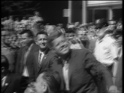 vidéos et rushes de b/w 1960s tracking shot president john f kennedy riding in convertible looking up waving - john fitzgerald kennedy