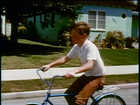 vídeos y material grabado en eventos de stock de 1960s tracking shot profile boy riding bicycle on suburban street / educational - bicicleta vintage