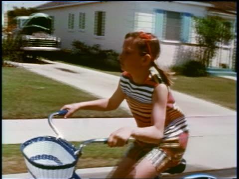vídeos y material grabado en eventos de stock de 1960s tracking shot profile girl riding bicycle on suburban street / educational - bicicleta vintage