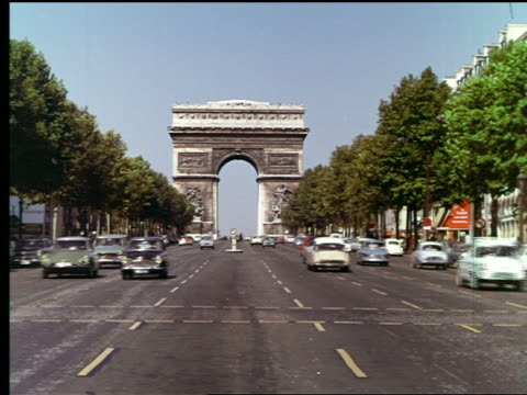 1960s traffic on tree-lined avenue des champs-elysees with arc de triomphe in background / paris, france - avenue des champs elysees stock videos & royalty-free footage