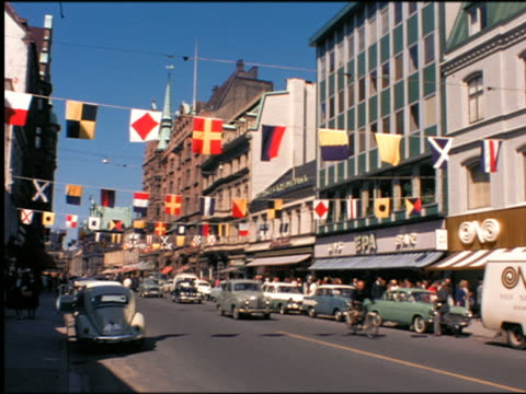 1960s traffic + people on city street with flags hanging across street / malmo, sweden - svezia video stock e b–roll