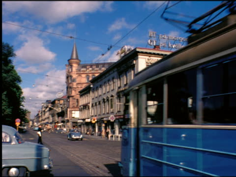 1960s trolley + traffic passing building on city street / Sweden