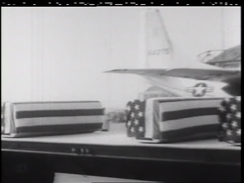 b/w 1960s pan truck carrying coffins covered in american flags at airport / vietnam war - 棺点の映像素材/bロール