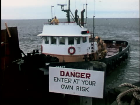 1960s ms, ha, tugboat moored in dock, warning sign in foreground, seattle, washington, usa - anno 1965 video stock e b–roll
