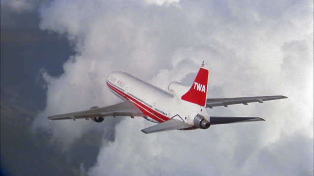 1960s TWA L1011 jet plane flying through clouds and over mountains