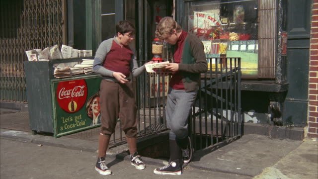 1960s ws two boys outside candy shop looking at magazine - zeitschrift stock-videos und b-roll-filmmaterial