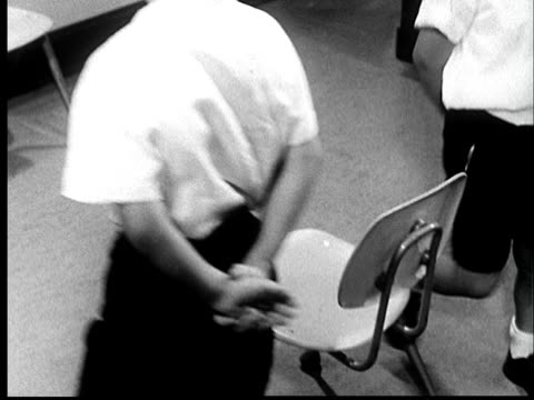 1960s ms two deaf boys with hearing aids playing musical chairs/ ms music stops and winning boy sits in chair/ st. louis - deafness stock videos and b-roll footage
