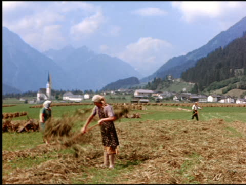 vídeos de stock, filmes e b-roll de 1960s two peasant women tossing hay with pitchfork in field / man + village in background / austria - áustria
